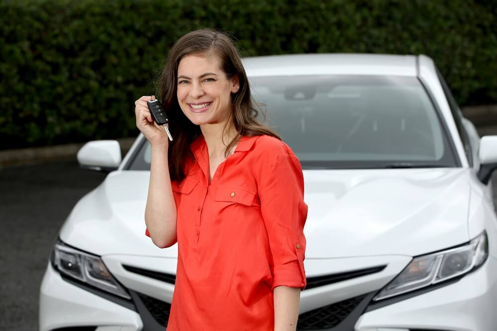 woman holding keys of a PCO rent to own car